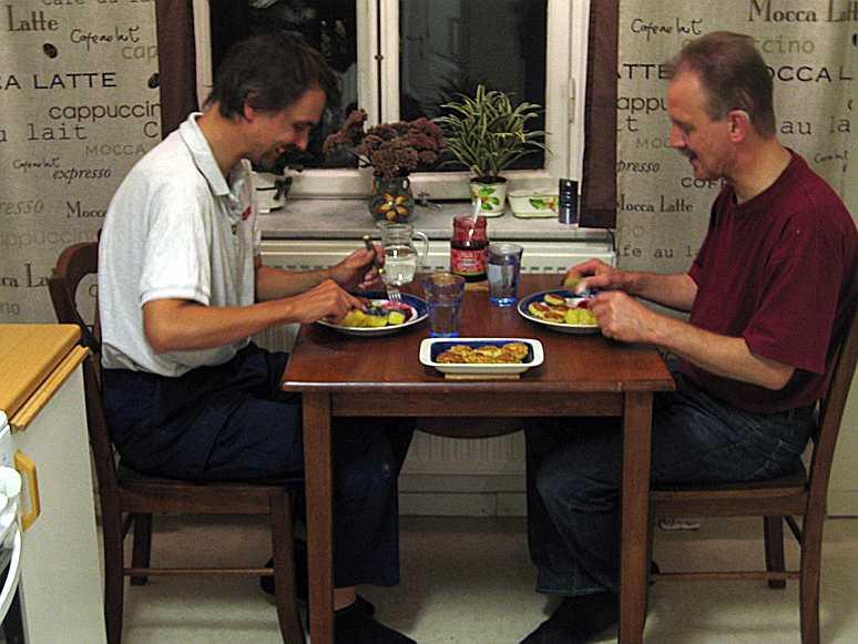 Två glada cykelreparatörer äter fiskbiffar till middag
